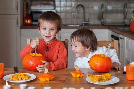 Two adorable boys, preparing jack o lantern for Halloween at home photo