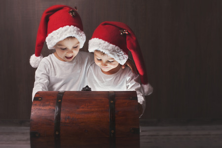 Two adorable boys, opening wooden chest, glowing light from inside, happy kids with santa hats photo