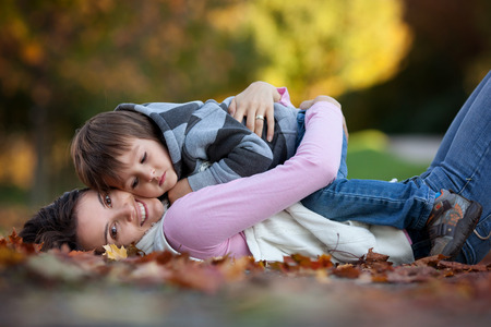 Young mom with her little boy in the park, lying on a path with autumn leaves photo