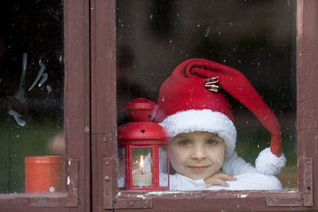 advent candles: Adorable boy, looking through window, waiting for Santa Stock Photo