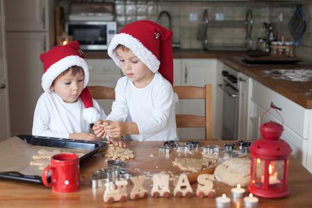 ginger cookies: Dos niños lindos con el sombrero de santa, la preparación de galletas en la cocina en el hogar Foto de archivo