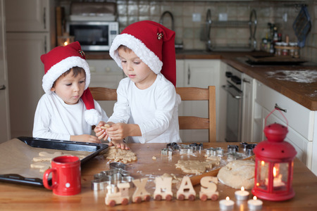 making fun: Two cute boys with santa hat, preparing cookies in the kitchen at home