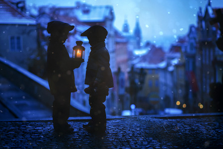 Silhouettes of two kids, standing on a stairs, holding a lantern, view of Prague behind them, snowy evening