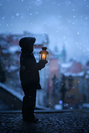 Silhouette of boy, standing on stairs, holding lantern, view of Prague behind him, snowy evening