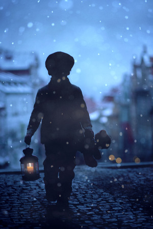 Silhouette of boy, standing on stairs, holding lantern and teddy bear, view of Prague behind him, snowy evening