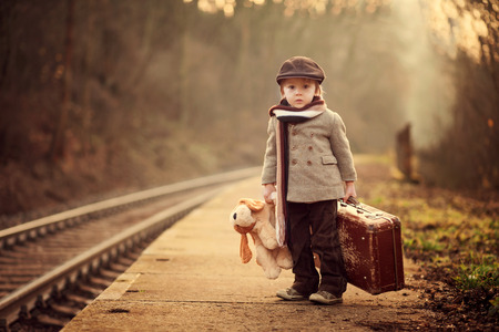 railroad transportation: Adorable boy on a railway station, waiting for the train with suitcase and teddy bear