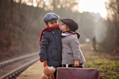 Two boys on a railway station, waiting for the train with suitcase and teddy bear photo