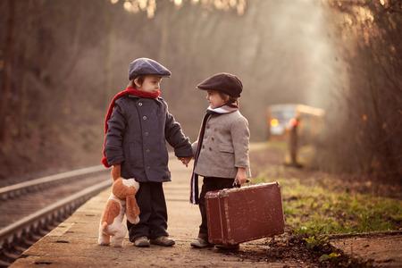 Twee jongens op een station, wachten op de trein met koffer en teddybeer Stockfoto