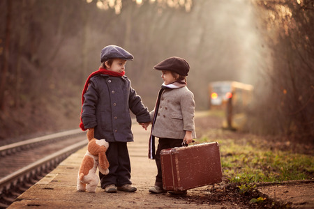 railway transportation: Two boys on a railway station, waiting for the train with suitcase and teddy bear