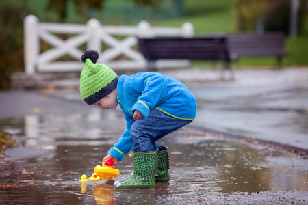 Little boy play with rubber ducks in the puddle