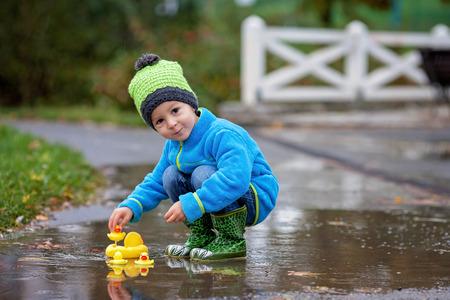botas de lluvia: Ni�o peque�o, saltar en los charcos fangosos en el parque, patos de goma en el charco Foto de archivo