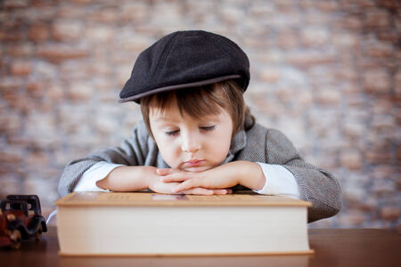 discover: Close portrait of boy with big book, indoor