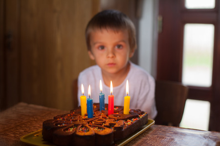 five year old: Adorable five year old boy celebrating his birthday and blowing