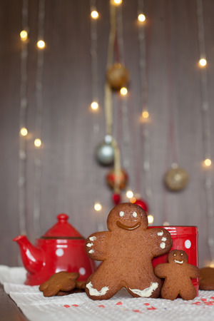 Smiling gingerbread man and a smaller one next to him standing in front of a mug. Teapot and more cookies on the background. Lights and christmas decoration in the background. Red and brown colors photo