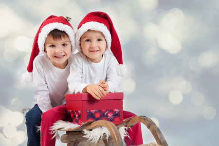 Two boys on christmas, having fun together, isolated on white