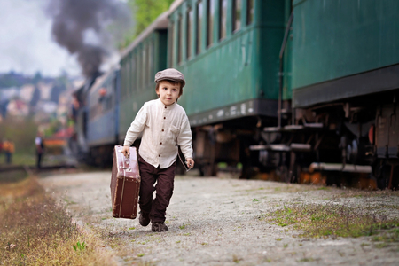 Boy dressed in vintage shirt and hat with suitcase on a railway station steam train photo