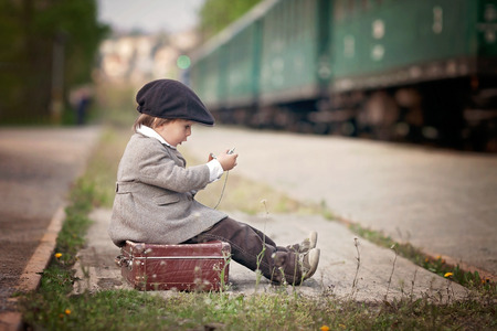 railway transportations: Boy, dressed in vintage coat and hat, with suitcase, on a railway station, steam train Stock Photo