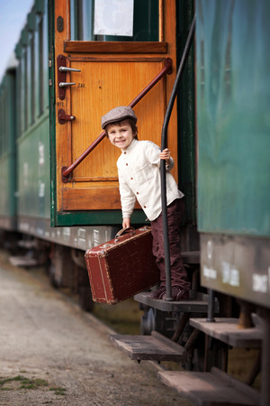 Boy dressed in vintage shirt and hat with suitcase on a railway station