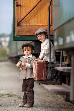 Two boys, dressed in vintage clothing and hat, with suitcase, on a railway station,sitting on steam train stairs photo