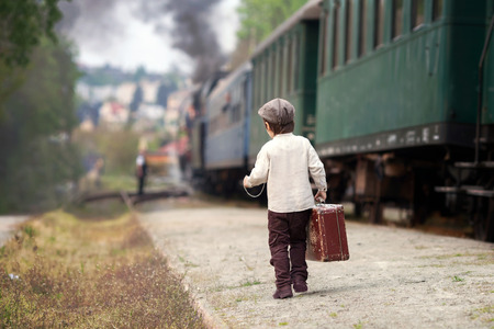 railway transportations: Boy, dressed in vintage shirt and hat, with suitcase, on a railway station, steam train Stock Photo