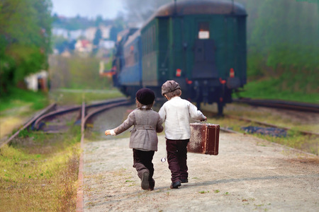 Two boys, dressed in vintage clothing and hat, with suitcase, on a railway station