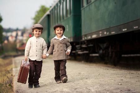 maquina vapor: Dos muchachos, vestidos con ropa y sombrero de época, con la maleta, en una estación de tren
