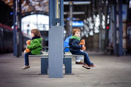 Two boys, sitting in a bench on the railway station, holding teddy bears photo
