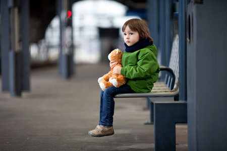 Cute boy, sitting on a bench with teddy bear, looking at a train, leaving the railway station photo