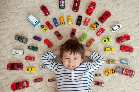 toy car: Adorable boy, lying on the ground, toy cars around him , looking at the camera, shot from above Stock Photo