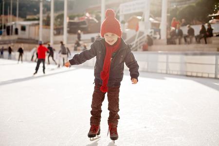 patinaje sobre hielo: Muchacho feliz con el sombrero rojo, patinaje durante el día, que se divierten