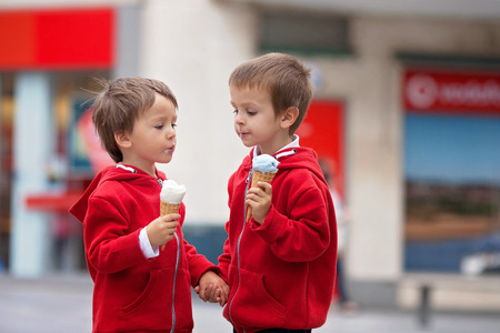 Two cute boys, eating ice cream on the street, tasting each others ice cream photo