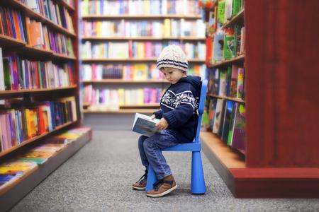 Schattige kleine jongen, zittend in een boekhandel, op zoek naar boeken