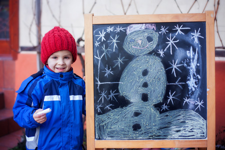 Adorable little boy, drawing winter picture with chalk on a board photo