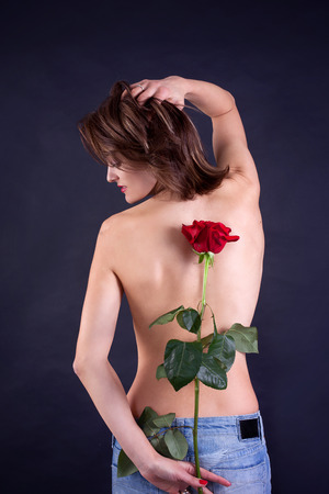 backwards: Portrait of attractive caucasian smiling woman isolated on black, studio shot, red rose, lips, smile, face, long hair, head and shoulders, eyes closed, backwards