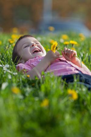 Cute little boy in a dandelion field, having fun