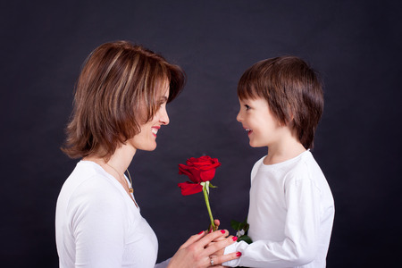 mother day: Young kid giving gorgeous red rose to his mom, studio shot isolated on black background Stock Photo
