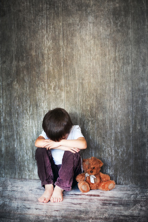 Young boy, sitting on the floor, teddy bear next to him, crying, looking away