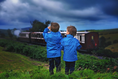Two boy, looking at old steam train, outdoor photo