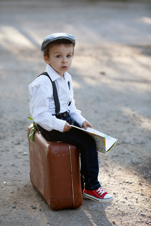Little boy with suitcase and map, traveling Standard-Bild