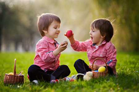 eyeing: Two boys in the park, having fun with colored eggs for Easter Stock Photo