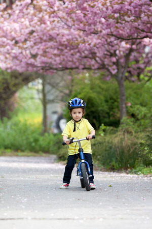 high visibility: Little boy playing with his bike outdoors in the park