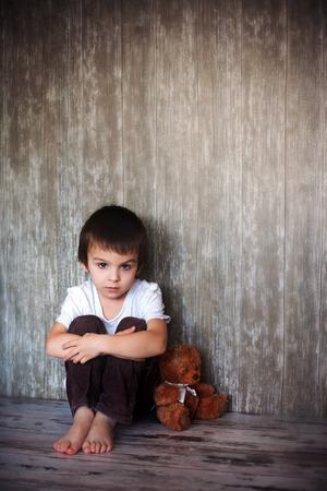 若い男の子は彼のテディー ・ ベアの床、彼の目に悲しみの上に座って