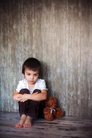his: Young boy, sitting on the floor with his teddy bear, sadness in his eyes