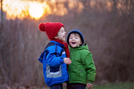 having fun in winter time: Two adorable boys, brothers, on a winter day, sunset time, smiling and having fun Stock Photo