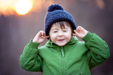 listen ear: Cute little boy, holding his hands over ears not to hear, making sweet funny face