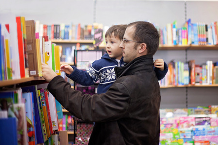 Adorable little boy, sitting in a book store, looking at books