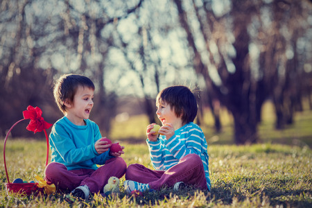 Two boys in the park, having fun with colored eggs for Easter, springtime photo