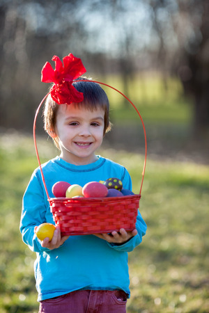 Adorable boy in the park, having fun with colored eggs for Easter, springtime photo