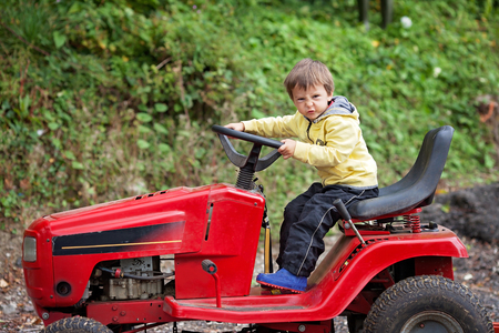 lawn mower: Adorable little boy, pretending to ride a lawn mower, making funny faces