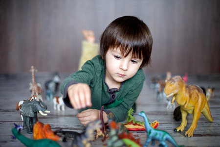 Beautiful little boy, smiling at camera, animals and dinosaurs around him, indoor shot